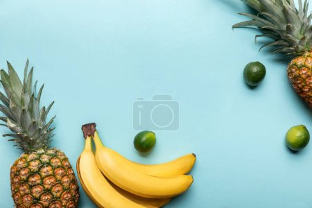 Photo for Top view of whole ripe pineapples, bananas and limes on blue background with copy space - Royalty Free Image