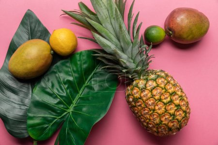 Photo for Top view of ripe exotic fruits with green leaves on pink background - Royalty Free Image