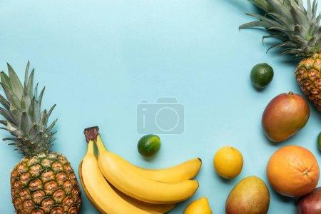 Photo pour Vue de dessus des fruits exotiques mûrs sur fond bleu avec espace de copie - image libre de droit