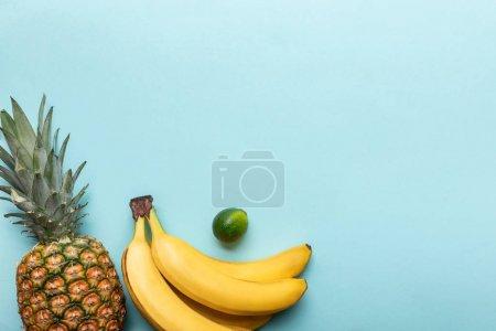 Foto de Top view of ripe pineapple, bananas and lime on blue background with copy space - Imagen libre de derechos