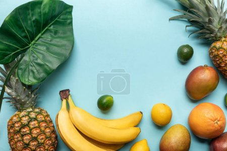 Photo for Top view of whole ripe tropical fruits with green leaf on blue background - Royalty Free Image