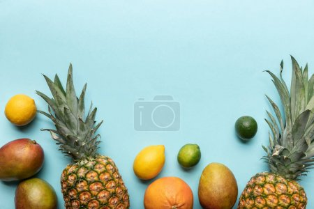 Photo for Top view of whole ripe tropical fruits on blue background - Royalty Free Image
