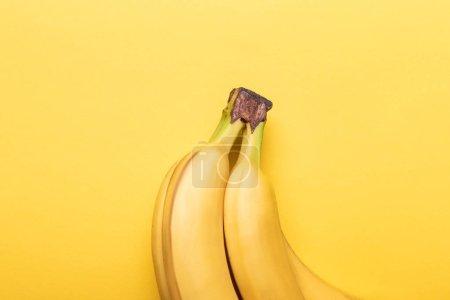 Foto de Top view of ripe bananas on yellow background - Imagen libre de derechos