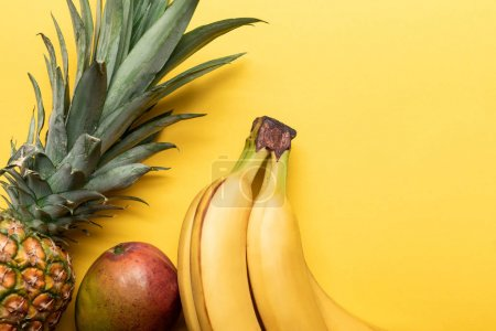 Photo for Top view of whole ripe bananas, pineapple and mango on yellow background - Royalty Free Image