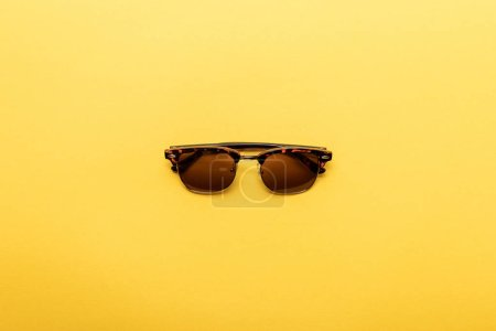 Photo for Top view of trendy sunglasses on yellow background - Royalty Free Image