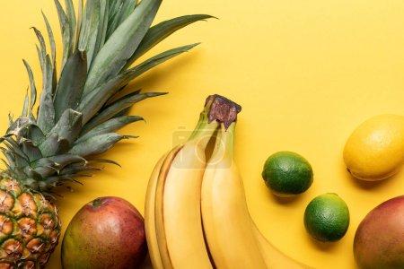 Photo pour Vue supérieure des bananes mûres entières, de l'ananas, des agrumes et de la mangue sur le fond jaune avec l'espace de copie - image libre de droit