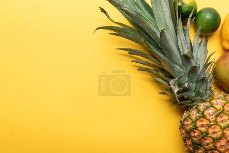 Foto de Vista superior de piña madura entera, cítricos y mango sobre fondo amarillo - Imagen libre de derechos