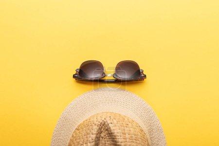 Foto de Vista superior del sombrero de verano de paja y gafas de sol sobre fondo amarillo - Imagen libre de derechos