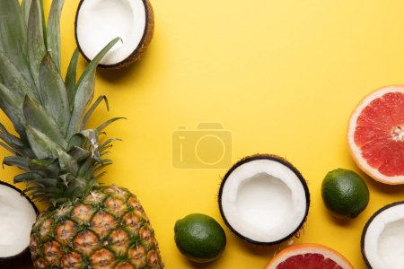 Photo for Top view of whole ripe pineapple, citrus fruits and coconut halves on yellow background - Royalty Free Image