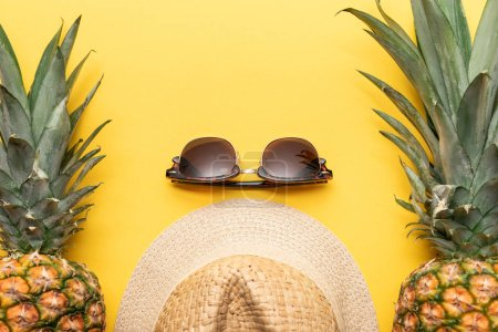 Photo for Top view of straw hat and sunglasses near pineapples on yellow background - Royalty Free Image