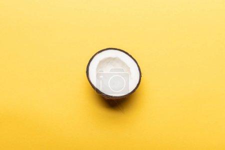 Photo pour Vue du dessus de la moitié de noix de coco mûre sur fond jaune avec espace de copie - image libre de droit