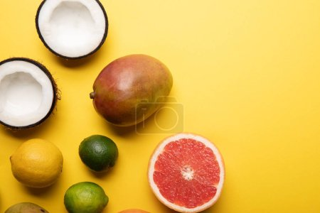 Photo for Top view of citrus fruits, mango and coconuts on yellow background with copy space - Royalty Free Image