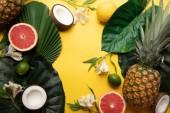 "Постер, картина, фотообои ""top view of ripe organic tropical fruits on yellow background with green leaves and Alstroemeria flowers"""