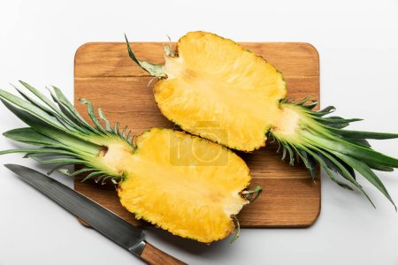 Photo for Top view of cut ripe yellow pineapple on wooden chopping board with knife on white background - Royalty Free Image