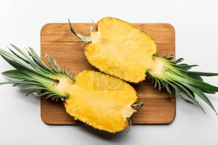 Photo for Top view of cut ripe yellow pineapple on wooden chopping board on white background - Royalty Free Image