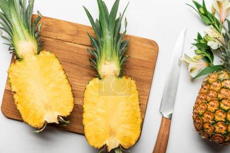 Photo pour Vue supérieure de l'ananas jaune mûr coupé sur la planche à découper en bois près du couteau et des fleurs d'Alstroemeria sur le fond blanc - image libre de droit
