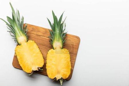 Photo pour Vue supérieure de l'ananas jaune mûr coupé sur la planche à découper en bois sur le fond blanc avec l'espace de copie - image libre de droit