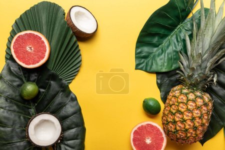 Photo for Top view of ripe organic exotic fruits on yellow background with green leaves - Royalty Free Image