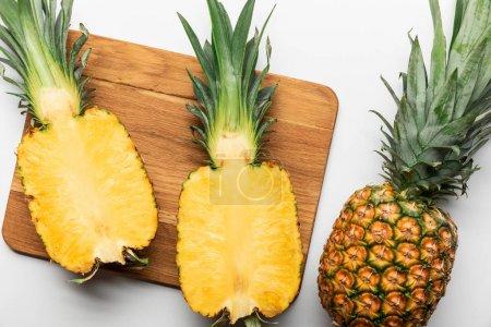 Photo pour Vue supérieure de l'ananas jaune mûr coupé sur la planche à découper en bois près du fruit entier sur le fond blanc - image libre de droit