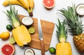 "Постер, картина, фотообои ""top view of cut and whole tropical fruits on wooden chopping board near knife on white background"""