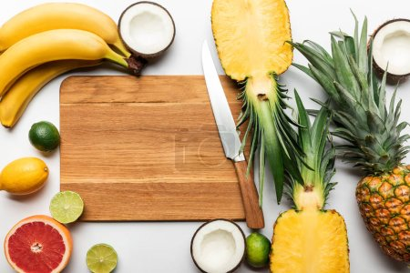 Photo for Top view of cut and whole tropical fruits on wooden chopping board with copy space near knife on white background - Royalty Free Image