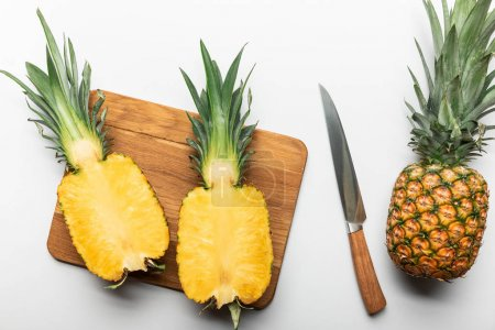 Photo pour Vue supérieure de l'ananas jaune mûr coupé sur la planche à découper en bois près du fruit entier et du couteau sur le fond blanc - image libre de droit