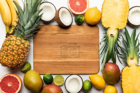 Photo for Top view of cut and whole tropical fruits around wooden chopping board with copy space on white background - Royalty Free Image