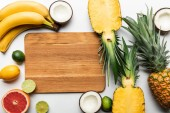 """Постер, картина, фотообои """"top view of exotic fruits around wooden chopping board with copy space on white background"""""""