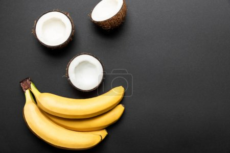 Photo for Top view of ripe yellow bananas and coconut halves on black background - Royalty Free Image