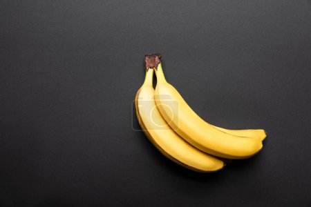 Photo for Top view of ripe yellow bananas on black background with copy space - Royalty Free Image