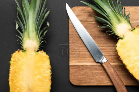 Photo for Top view of cut ripe pineapple on wooden chopping board with knife on black background - Royalty Free Image