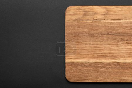Photo for Top view of empty wooden cutting board on black background - Royalty Free Image