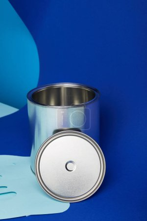Foto de Silver can on dripping paper cut paint on bright blue background - Imagen libre de derechos