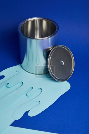 Photo for Silver shiny can and dripping paper cut paint on bright blue background - Royalty Free Image