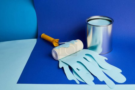 Photo for Metal can and roller with dripping paper cut paint on bright blue background - Royalty Free Image