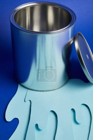 Photo for Empty metal shiny can and dripping paper cut paint on bright blue background - Royalty Free Image
