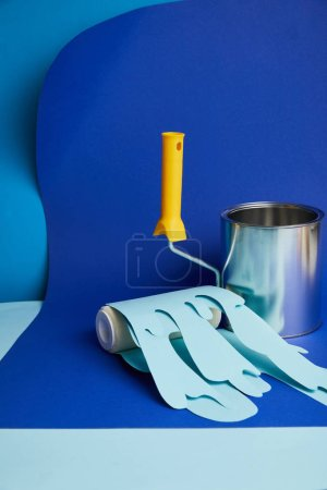 Photo for Empty shiny can near roller with dripping paper cut paint on bright blue background - Royalty Free Image