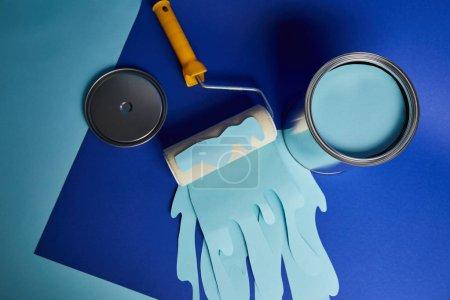 Photo pour Vue supérieure du métal brillant peut près du rouleau avec la peinture de coupe de papier dégoulinant sur le fond bleu lumineux - image libre de droit