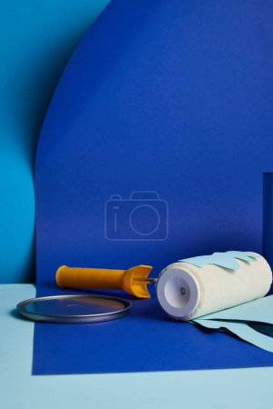 Photo for Metal cap near roller with dripping paper cut paint on bright blue background - Royalty Free Image