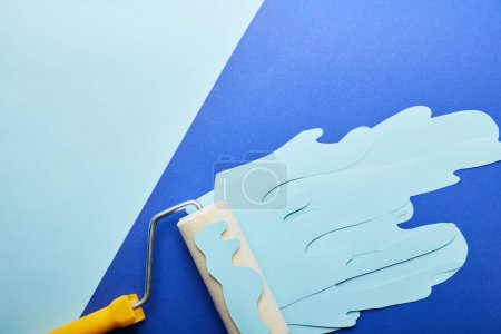 Photo for Top view of roller with blue paper cut dripping paint - Royalty Free Image