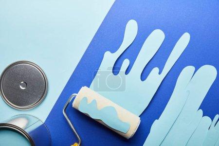 Photo pour Vue supérieure du chapeau brillant en métal, peut et papier bleu coupé la peinture dégoulinante près du rouleau - image libre de droit