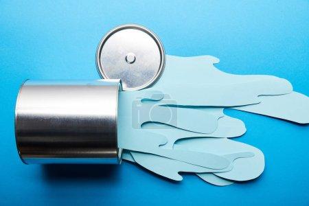 Foto de Vista superior de papel derramado cortado pintura azul cerca de plata brillante lata y la tapa - Imagen libre de derechos