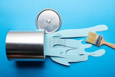 Photo for Top view of spilled paper cut blue paint from silver can near brush and cap - Royalty Free Image