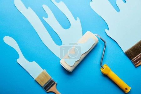 Photo for Top view of roller and brushes with dripping paper cut paint on bright blue background - Royalty Free Image