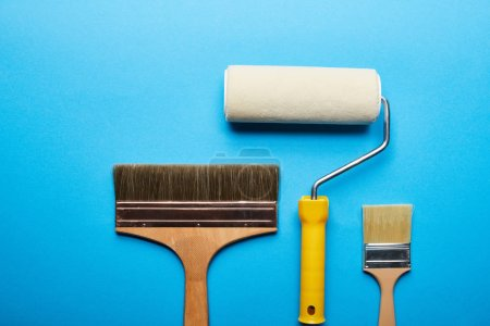 Photo for Top view of roller and brushes on blue bright background with copy space - Royalty Free Image
