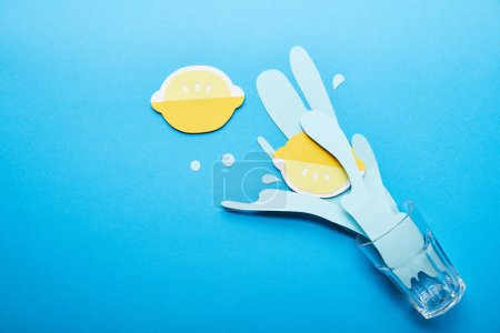 Foto de Top view of glass with paper cut water splash and lemons on blue background with copy space - Imagen libre de derechos