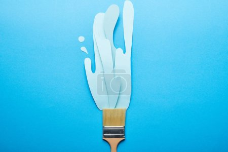Photo for Top view of brush with dripping paper cut paint on bright blue background - Royalty Free Image