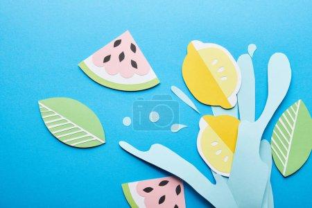 Photo pour Vue supérieure de papier éclabousser l'eau coupée avec des citrons, des feuilles et des pastèques sur le fond bleu - image libre de droit