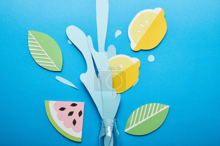 Photo for Top view of bottle with paper cut water splash, lemons, leaves and watermelon on blue background - Royalty Free Image