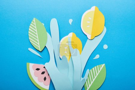 Photo for Top view of paper cut water splash with lemons, leaves and watermelon on bright blue background - Royalty Free Image
